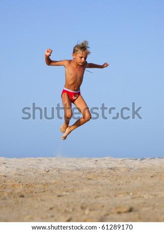 The boy jumps up on the sandy beach near the sea