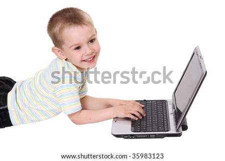 The boy lays behind the laptop looks and smiles