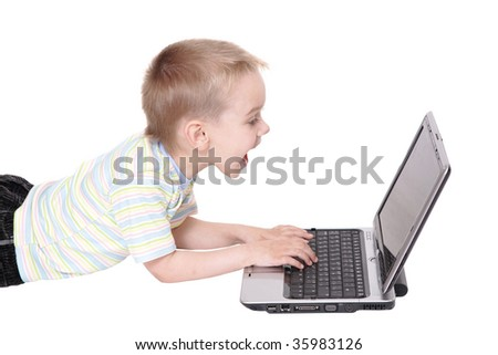 The boy lays in front of the laptop and shouts