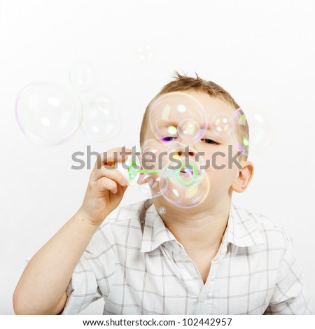 The boy lets go soap bubbles. The little boy and soap bubbles. Carefree.