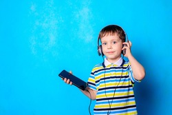 The boy listens to music with headphones on his phone . Emotions boy. Blue background. A boy wearing headphones. Listen to music. Children's fairy tales in headphones. Training.
