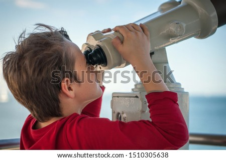 the boy looks through a tourist telescope at the sky