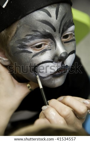 The boy makes a children's make-up, perhaps it is the cat