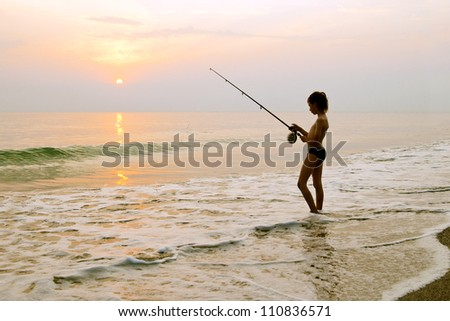 The boy on the background of the dawn sun, spinning fishing.