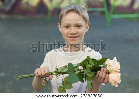 The boy on the street with flowers, presents flowers, smiling