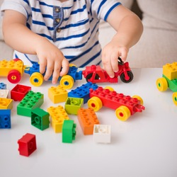 The boy plays colorful multi-colored cubes on the table. Early development and learning. Bright constructor for the game of plastic bricks.