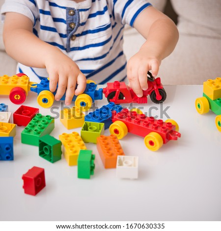 The boy plays colorful multi-colored cubes on the table. Early development and learning. Bright constructor for the game of plastic bricks. Foto stock ©