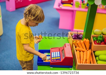 The boy plays with the children's cash register. financial literacy for children