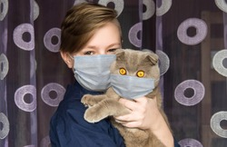 The boy put a medical mask on himself and his pet cat. Quarantine. Beautiful young boy with a cat breeder. Embrace with a fluffy friend.