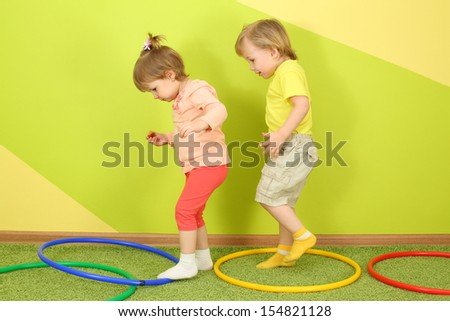 The boy runs after a girl in a bright room, on the floor are colored hoops