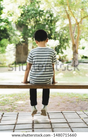The boy sat sadly alone on the bench #1480715660