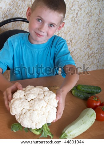 The boy sits at a table with vegetables