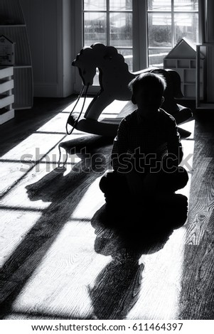 The boy sits on the floor in the nursery next to the rocking horse