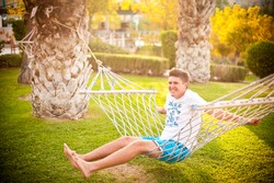 The boy sits on the hammock