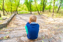 The boy sits on the old steps in the park and looks down, view from the back.