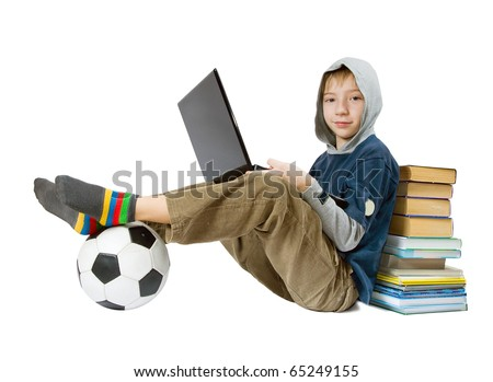 The boy sits with the laptop, a ball, books
