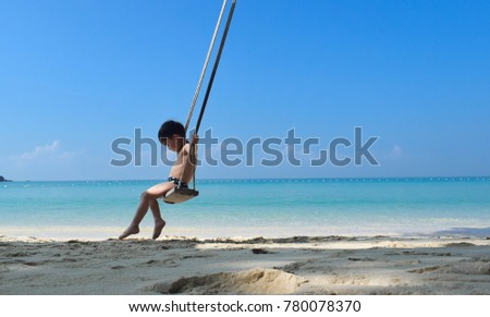 The boy sitting on a swing at the beach in Thailand. #780078370