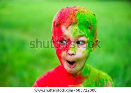 The boy smeared with paints of holi. Surprised by what is happening. Vivid, emotions, surprises and admiration #683922880