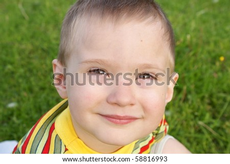 The boy smiles, background green grass,portrait
