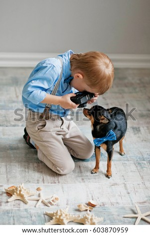 The boy takes pictures of the dog