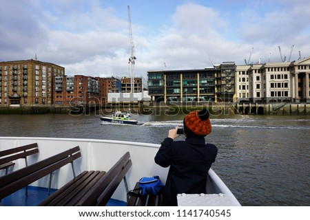 The Boy taking pictures of London with Police Boat. The popular boat trip on the Thames in Capital City of England. Beautiful View of Historic Highlights at sunny day in winter.