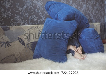 the boy the child has constructed the house from pillows on a sofa, crisis of negativism,Behavior Problems depression. Gray-blue tone, life style in a real interior.