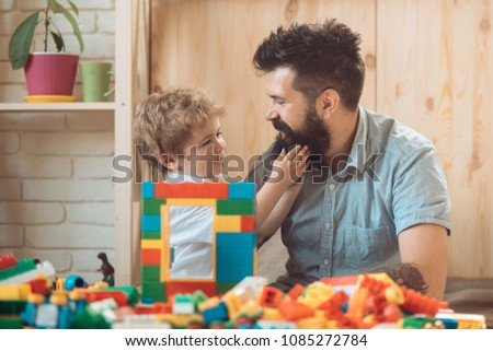 The boy touches his father's beard. An example and love. Tender feelings, family love. A good father. Father's Day. The son and father spend time together at home. A caring parent #1085272784