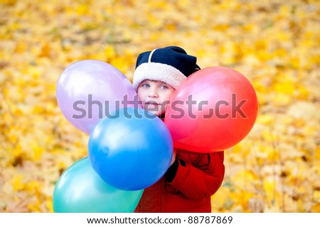 The boy walks at autumn in park with inflatable balls