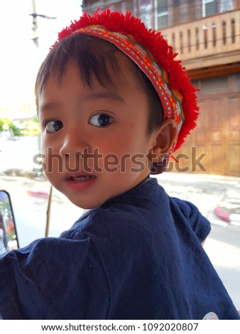 The boy wears a blue Thai folk costume wearing a red hat.in Thailand #1092020807