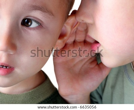 The boy whispering in an ear to the younger brother.
