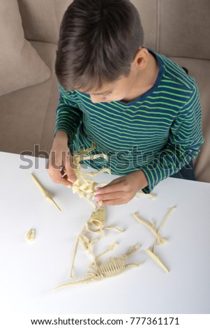 the boy with enthusiasm collects a skeleton of a dinosaur #777361171