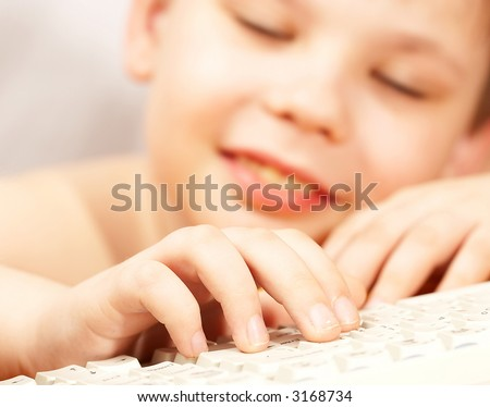 The boy with the keyboard at a computer