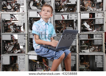 The boy works behind a portable computer on a background of a wall from old computers. Horizontal orientation.