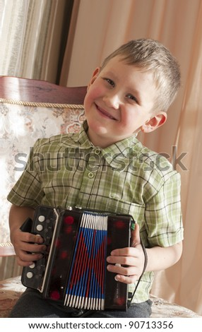 The boy (5 years) plays an accordion