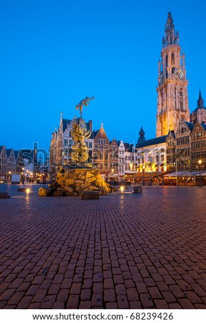 The Brabo statue and cathedral of Our Lady (Onze Lieve) at twilight blue hour in the Grote Markt square old city center in Antwerp, Belgium