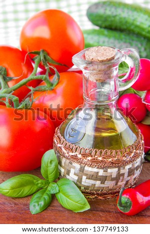 The branch of fresh tomatoes, cucumbers, radishes and a bottle of olive oil on table