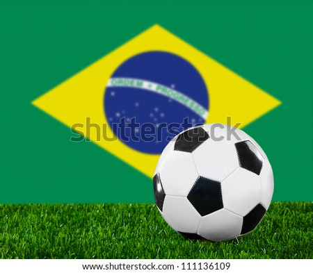 The Brazilian flag and soccer ball on the green grass
