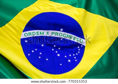 """The Brazilian flag in fabric, with a close up of the blue disc depicting a starry sky  spanned by the national motto """"Ordem e Progresso""""  (""""Order and Progress""""), within a yellow rhombus, on green.  #770315353"""