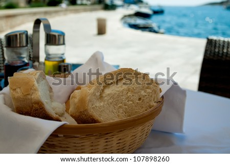 The bread and olive oil is standing on the table next to the ocean.