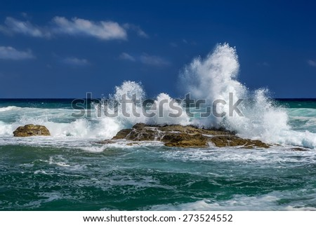 The breaking waves forming a spray and a stony beach
