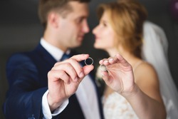 The bride and groom are holding wedding rings. Wedding rings close-up. Focus on wedding rings, unfocus the bride and groom