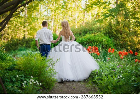 The bride and groom are in the park holding hands around the beautiful flower beds of poppies and white flowers