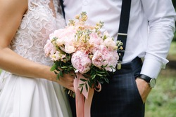 the bride and groom are standing close to each other, the bride is holding a bouquet of pink peonies.