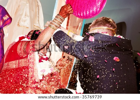 The bride and groom dump rice on each other during a traditional Hindu wedding ceremony