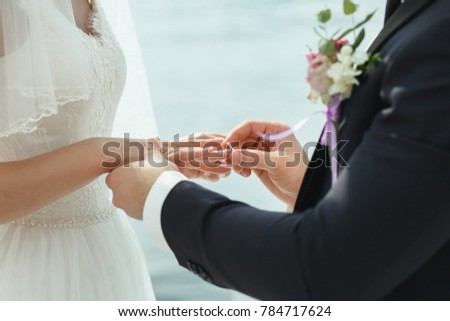 the bride and groom exchange rings #784717624