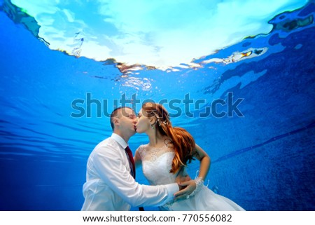00c1c36621b50 The bride and groom in wedding dresses embrace and kiss underwater in the  pool on a
