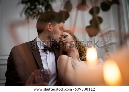 the bride and groom sit in each other's arms, photographed through the leaves and candles #609508112