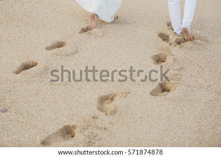 The bride and groom walk hand in the sand. footprints in the sand near the ocean