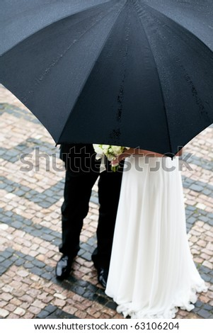 the bride and groom with a bouquet of flowers under the umbrella - stock photo