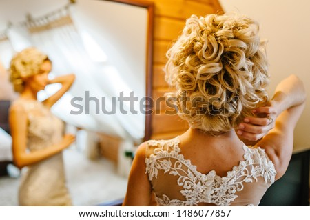 The bride corrects hairdo at his head. A look on the back of the woman's hands and hair. Wedding Morning.